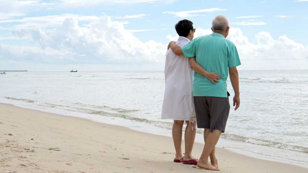 Asian senior couple walking together on the beach by the sea